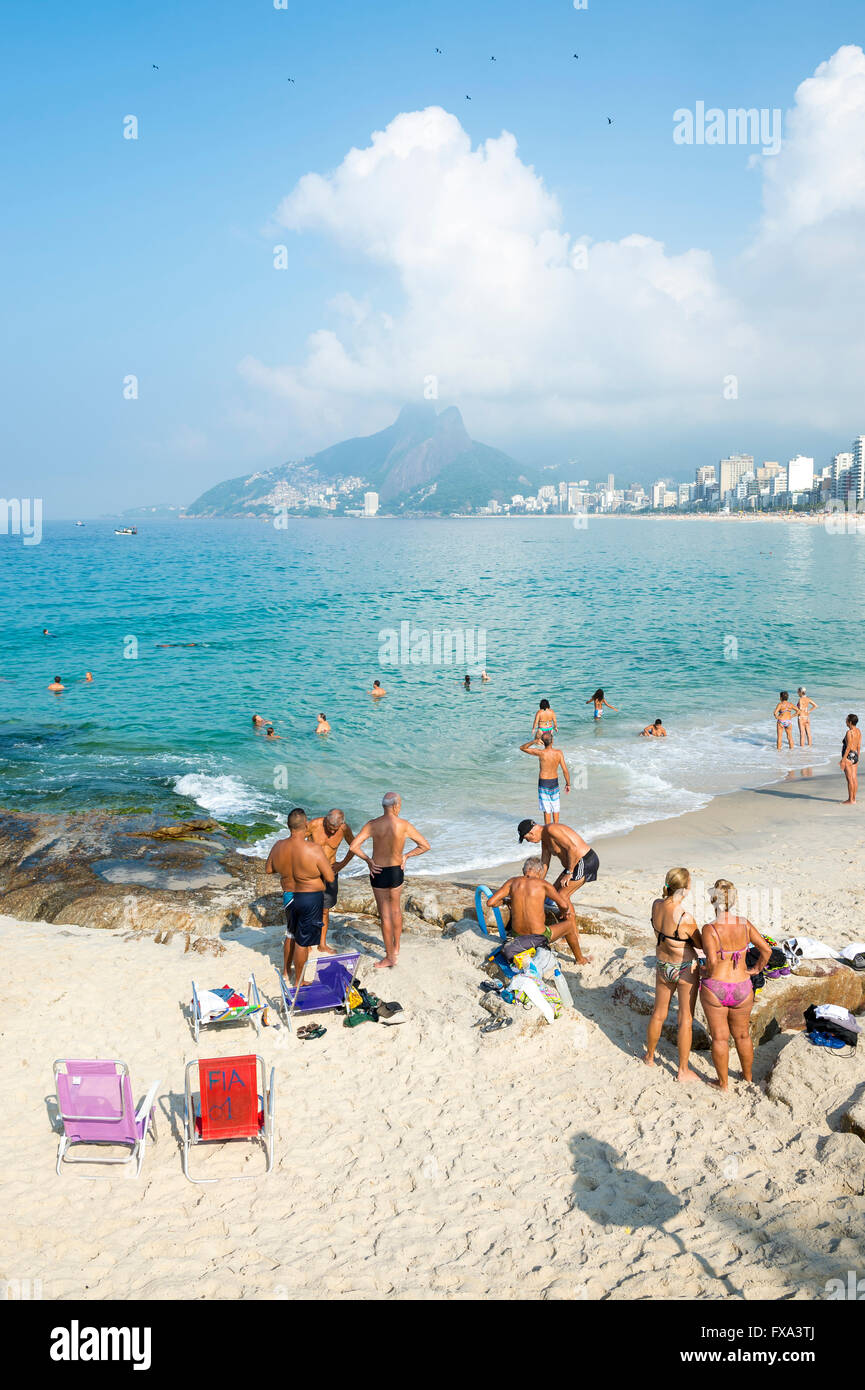 RIO DE JANEIRO - APRIL 5, 2016: Beachgoers sunbathe on a calm morning at the Arpoador end of Ipanema Beach. Stock Photo