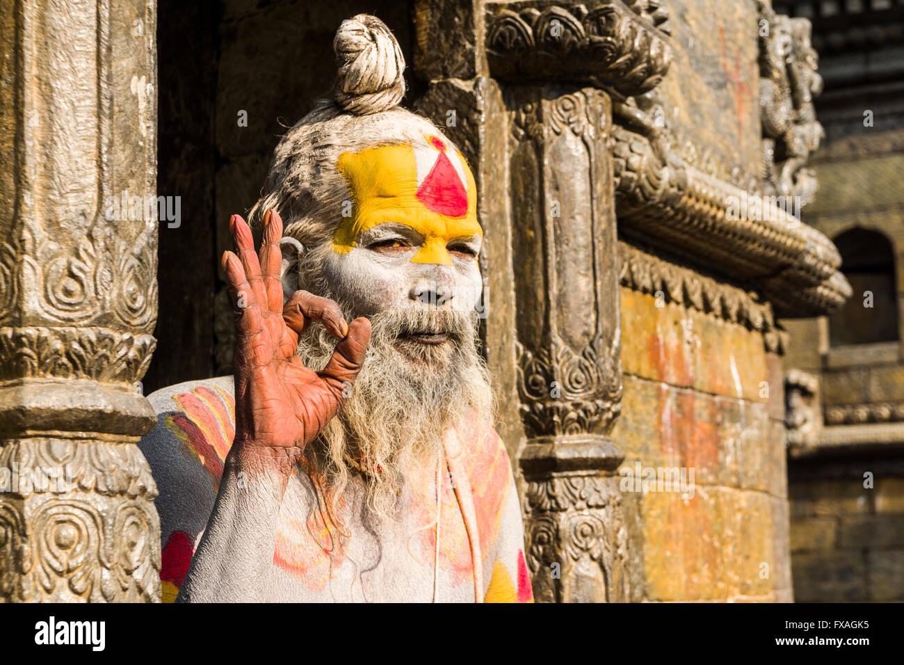 The portrait of a Sadhu, holy man, sitting in a doorway of Pashupatinath Temple, Kathmandu, Nepal Stock Photo