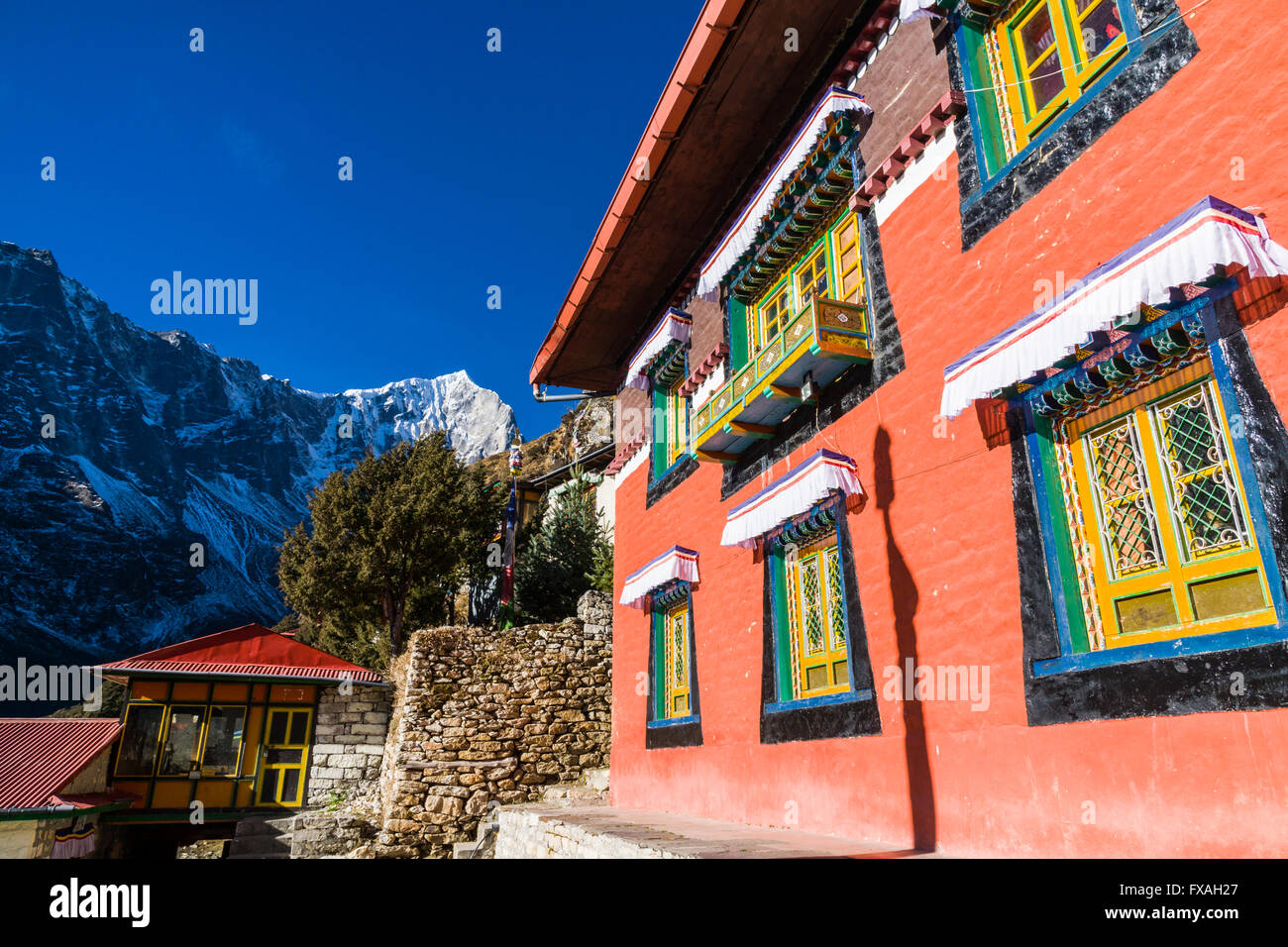 Colourful buildings of the Thame Gompa monastery, situated on a mountain slope, snow covered mountains in the distance, - Stock Image