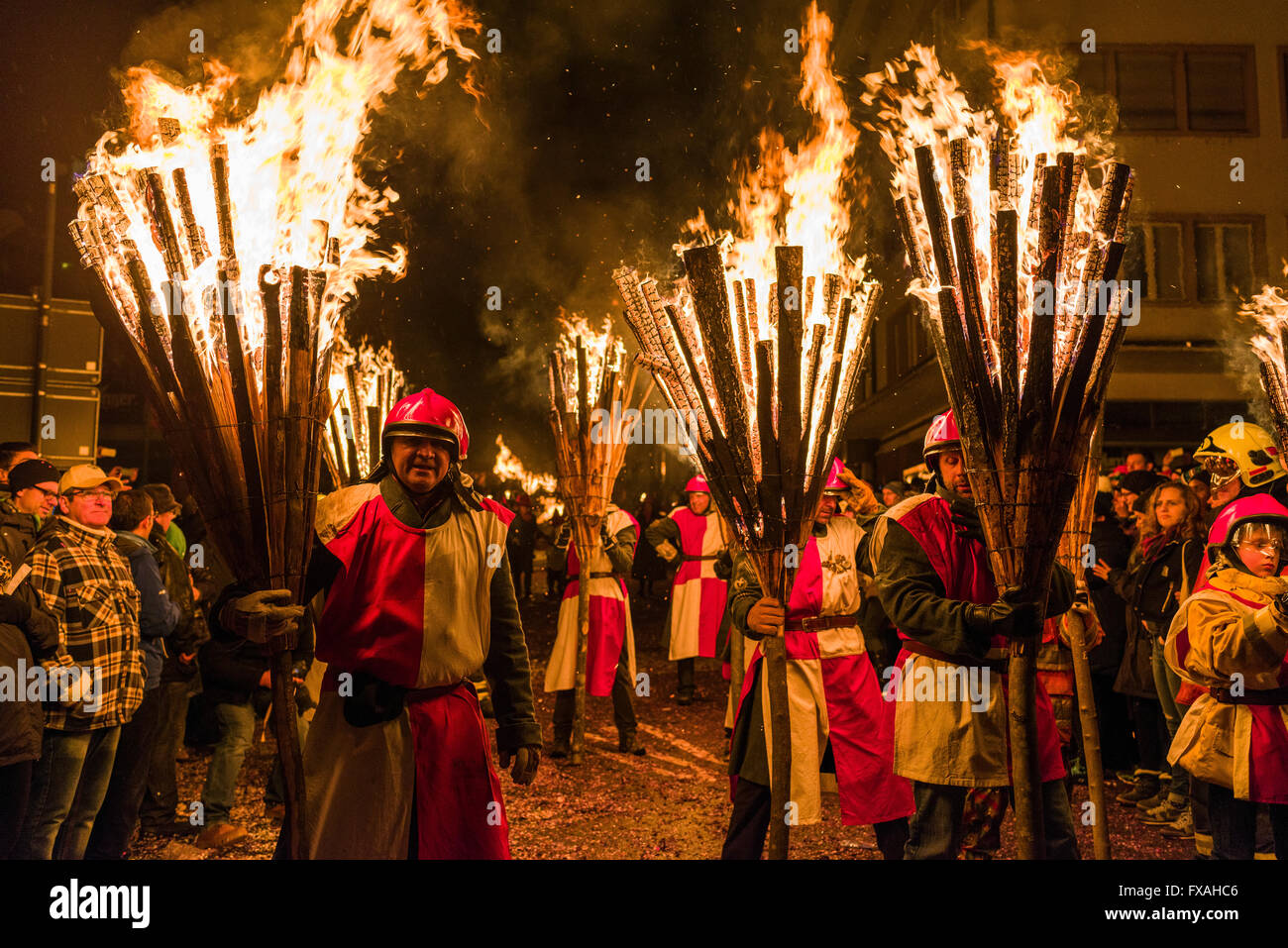 Procession of people carrying burning pinewood bundles called Chienbäse, Carnival of Basel, Basler Fasnacht, - Stock Image