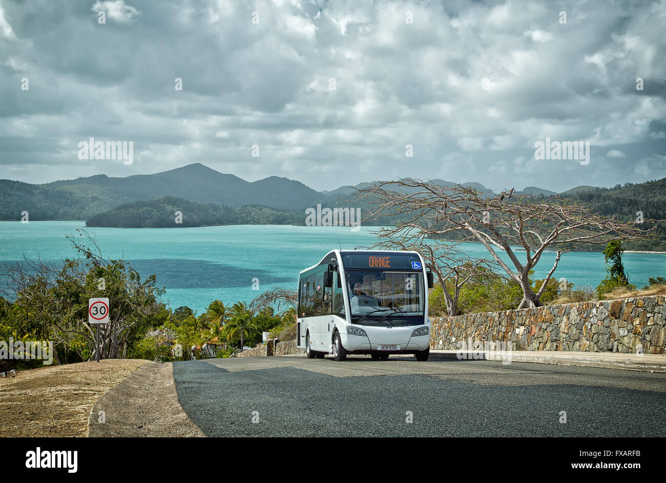A complimentary bus service conveys holidaymakers around Hamilton island. Golf buggies and buses are the only vehicles - Stock Image