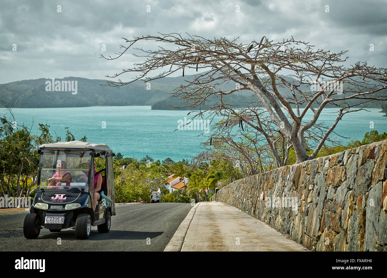 Two women drive a golf buggy to their destination. Golf buggies and complimentary buses are the only vehicles available - Stock Image