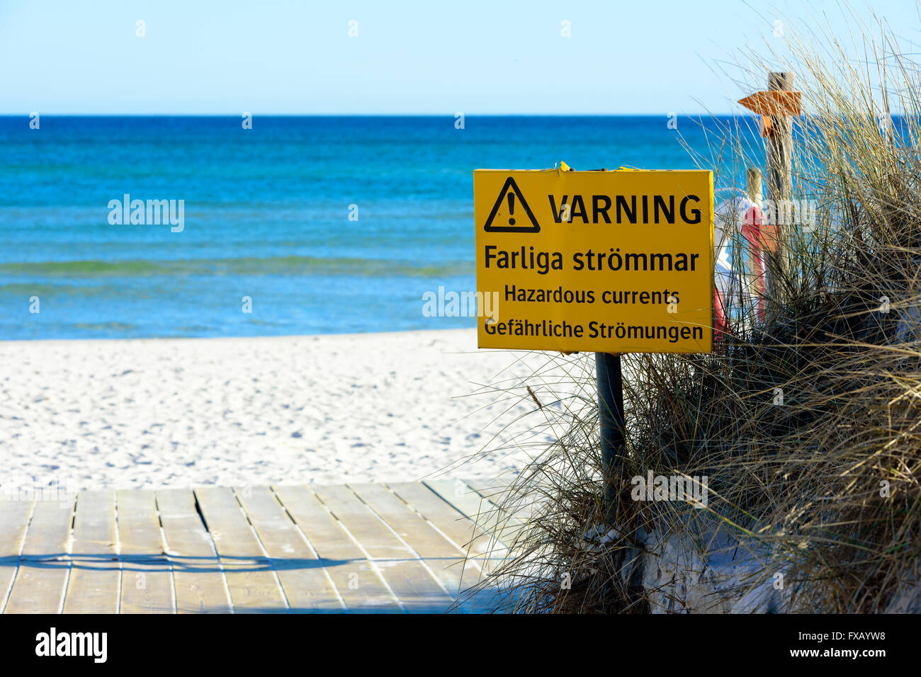 Sandhammaren, Sweden - April 1, 2016: Yellow warning sign about hazardous currents in the water at a sandy beach - Stock Image