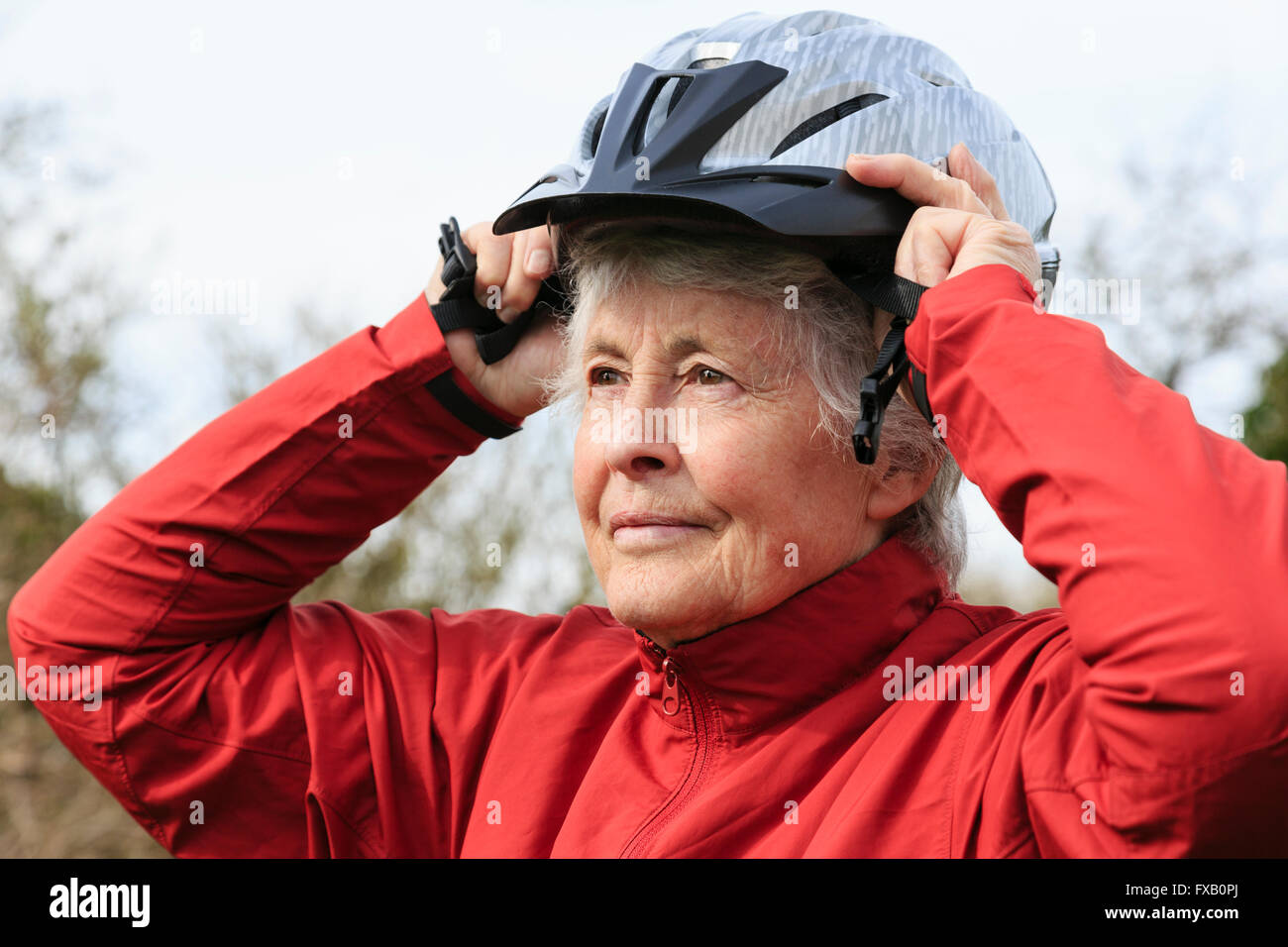 Active elderly senior retired woman putting on a bike cycling helmet preparing to go for a cycle ride to keep fit - Stock Image
