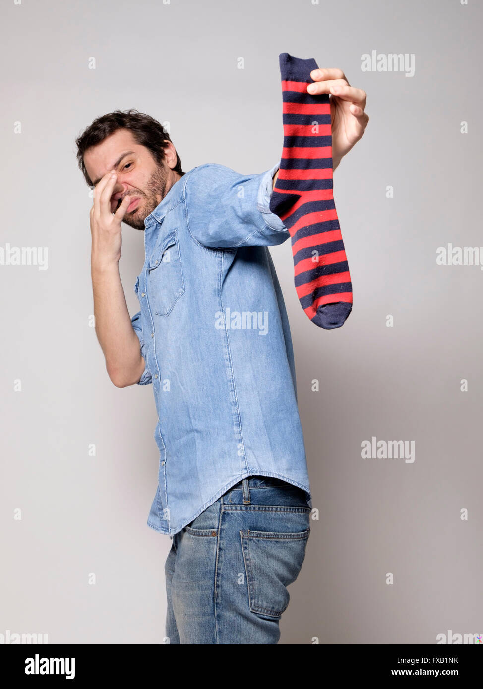 Man smelling a stinky sock - Stock Image