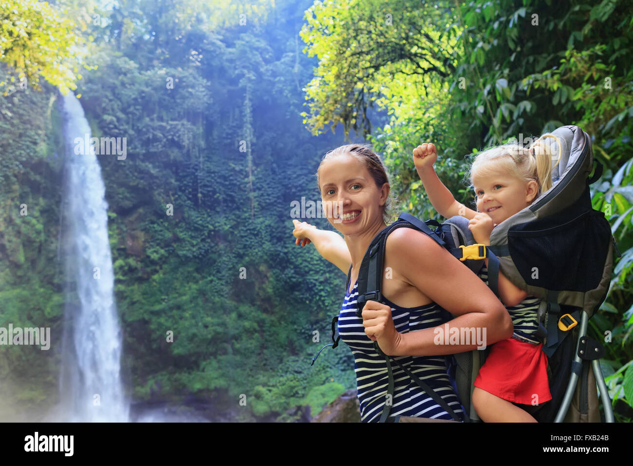 Mother hold baby girl on back in carrying backpack walking in waterfall canyon. - Stock Image