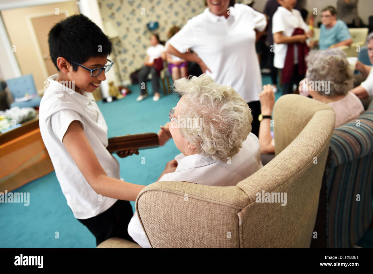 School children visit the elderly in a care home to foster good relations between the generations - Stock Image