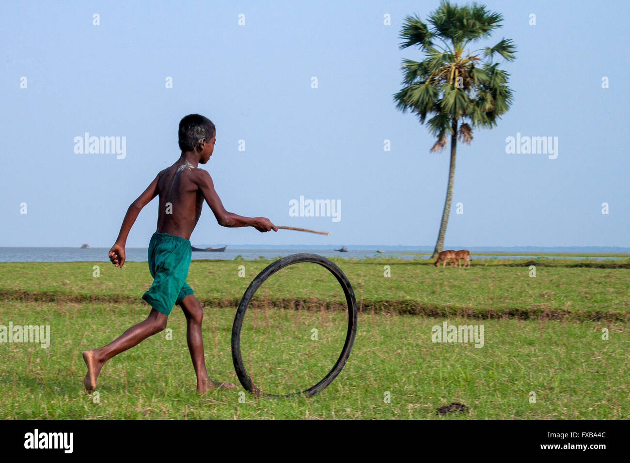 A boy playing with bicycle tire in the Vola District, Barishal, Bangladesh, Asia © Jahangir Alam Onuchcha/Alamy - Stock Image