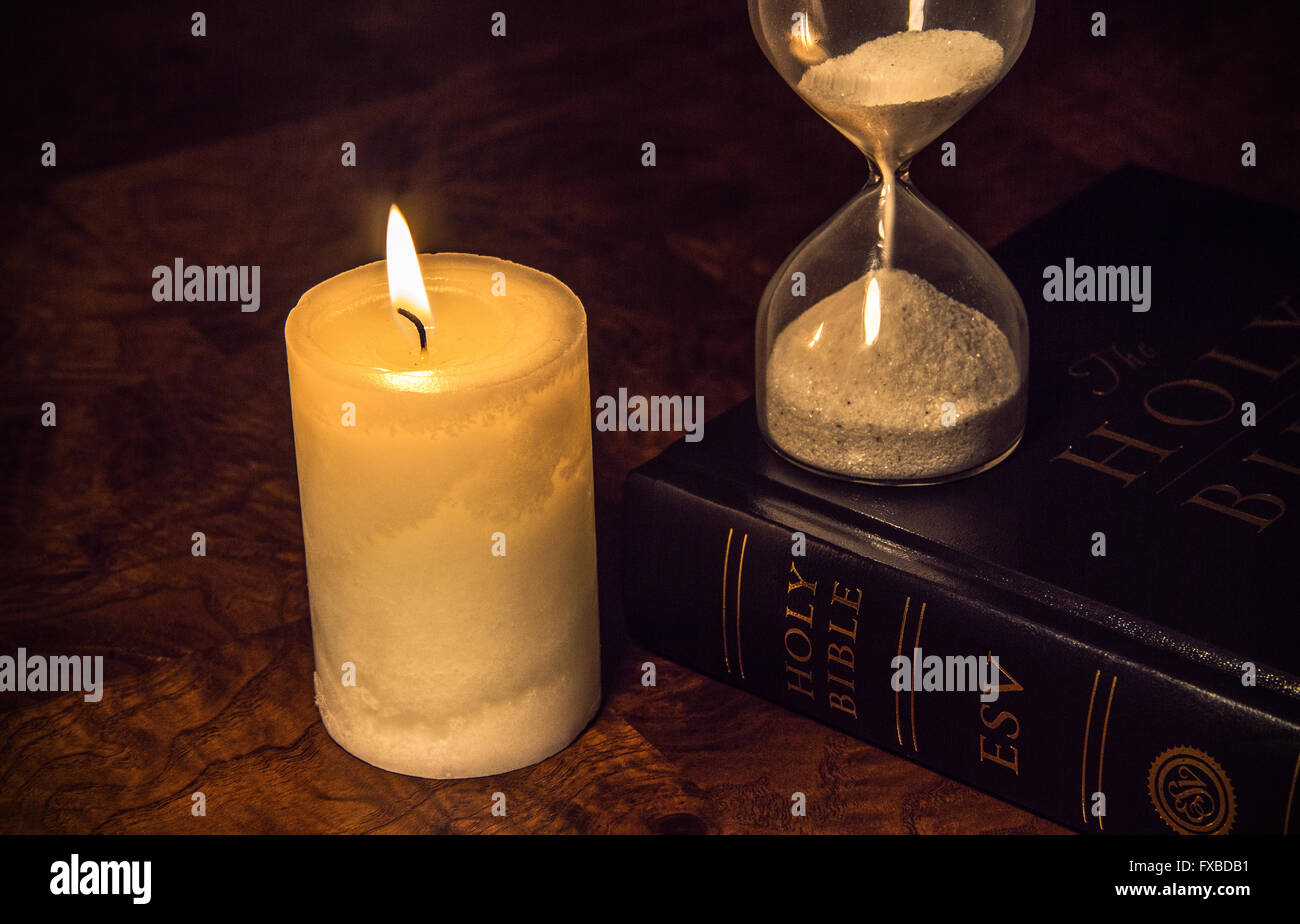 Bible & hourglass symbol of the end of times. - Stock Image