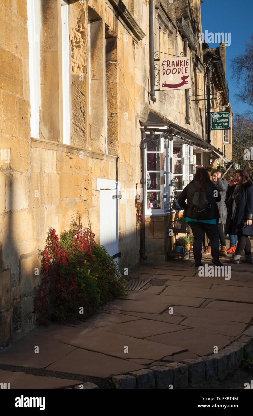 Group of young female tourists window shopping in the High Street of Chipping Campden in December, Cotswolds, Gloucestershire, - Stock Image