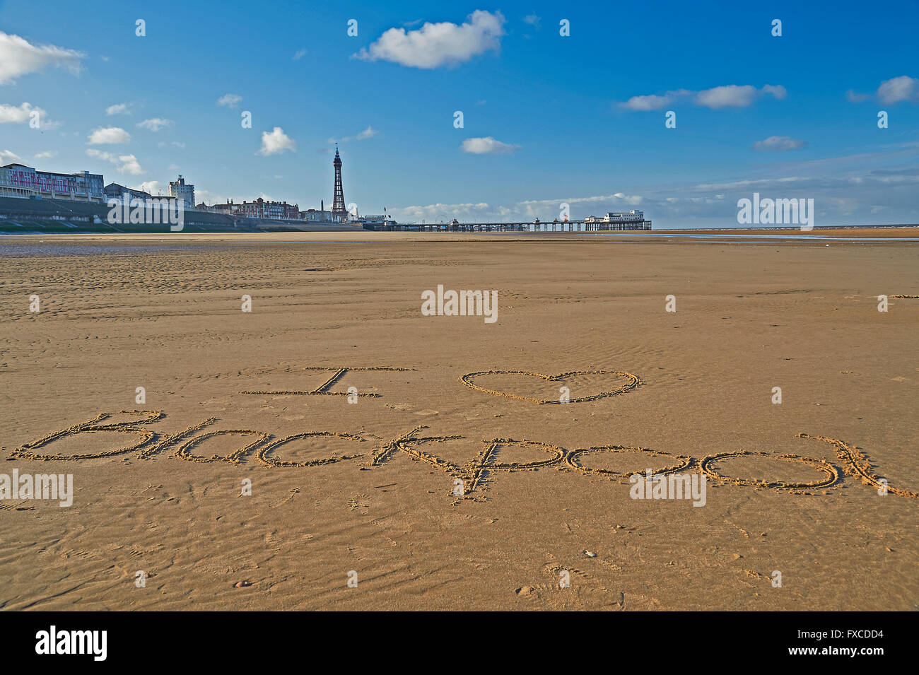 I love Blackpool written on the sand with Blackpool Tower and  North Pier - Stock Image