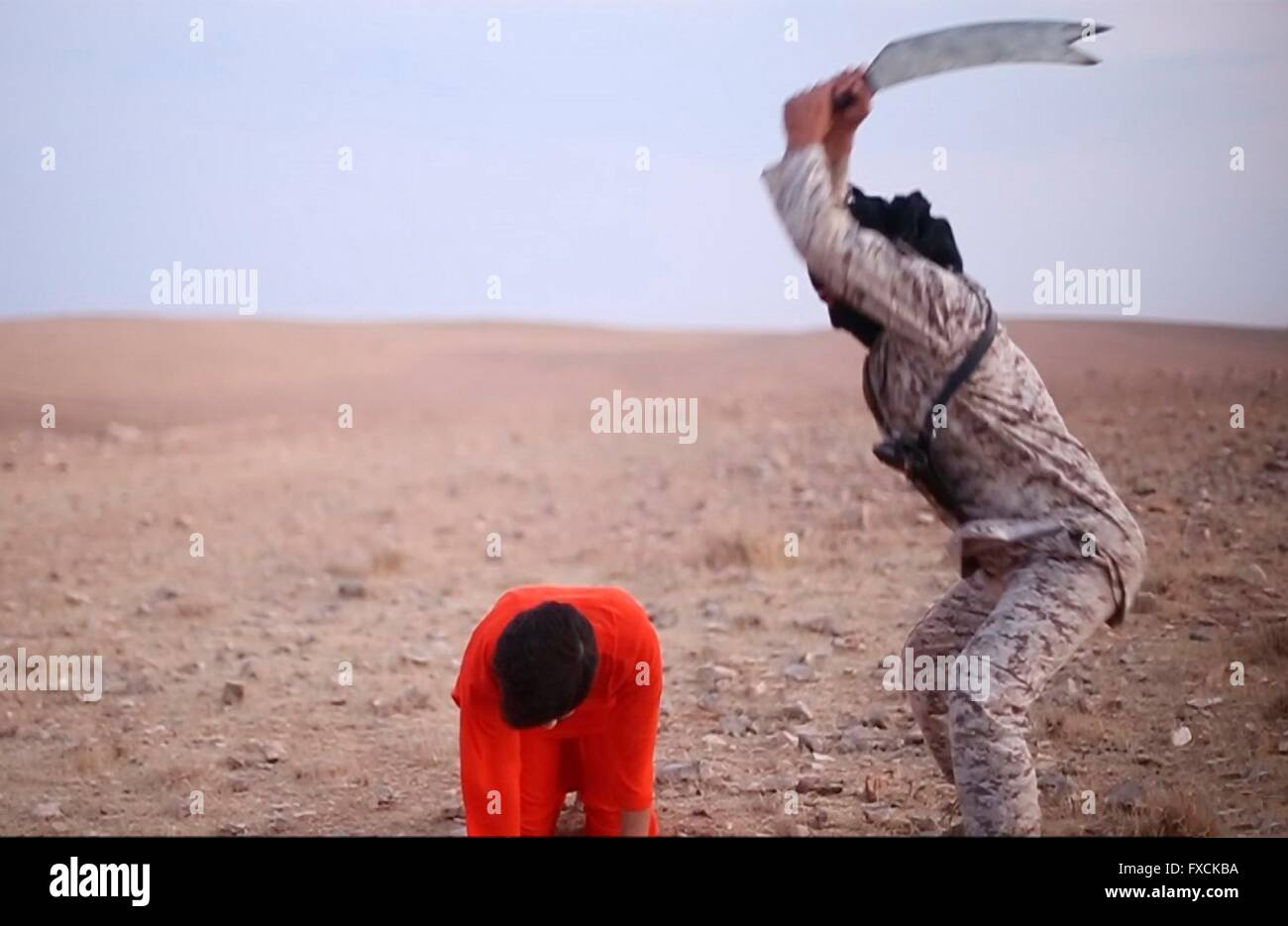 Islamic State fighter beheads an alleged spy in a propaganda video capture released by the Islamic State of Iraq - Stock Image