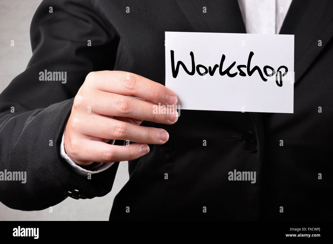 Businessperson holding a card with workshop written on it - Stock Image