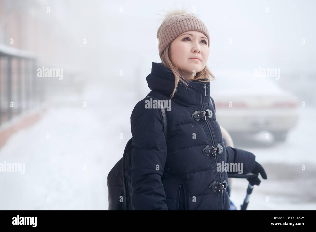 Young woman with stroller walking in winter, looks thoughtfully at sky. - Stock Image