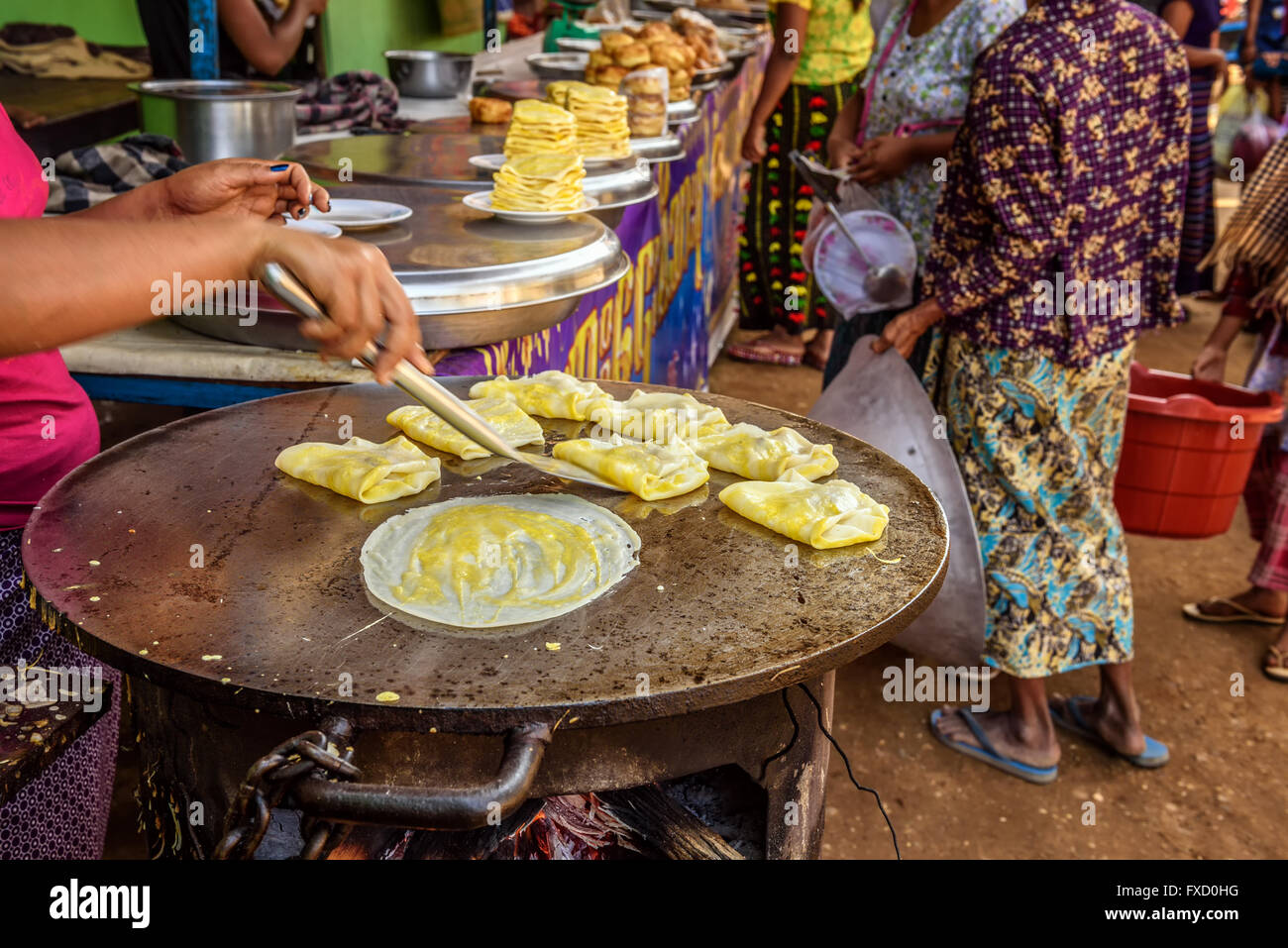 Asian cook prepares traditional Burmese street food in Myanmar - Stock Image