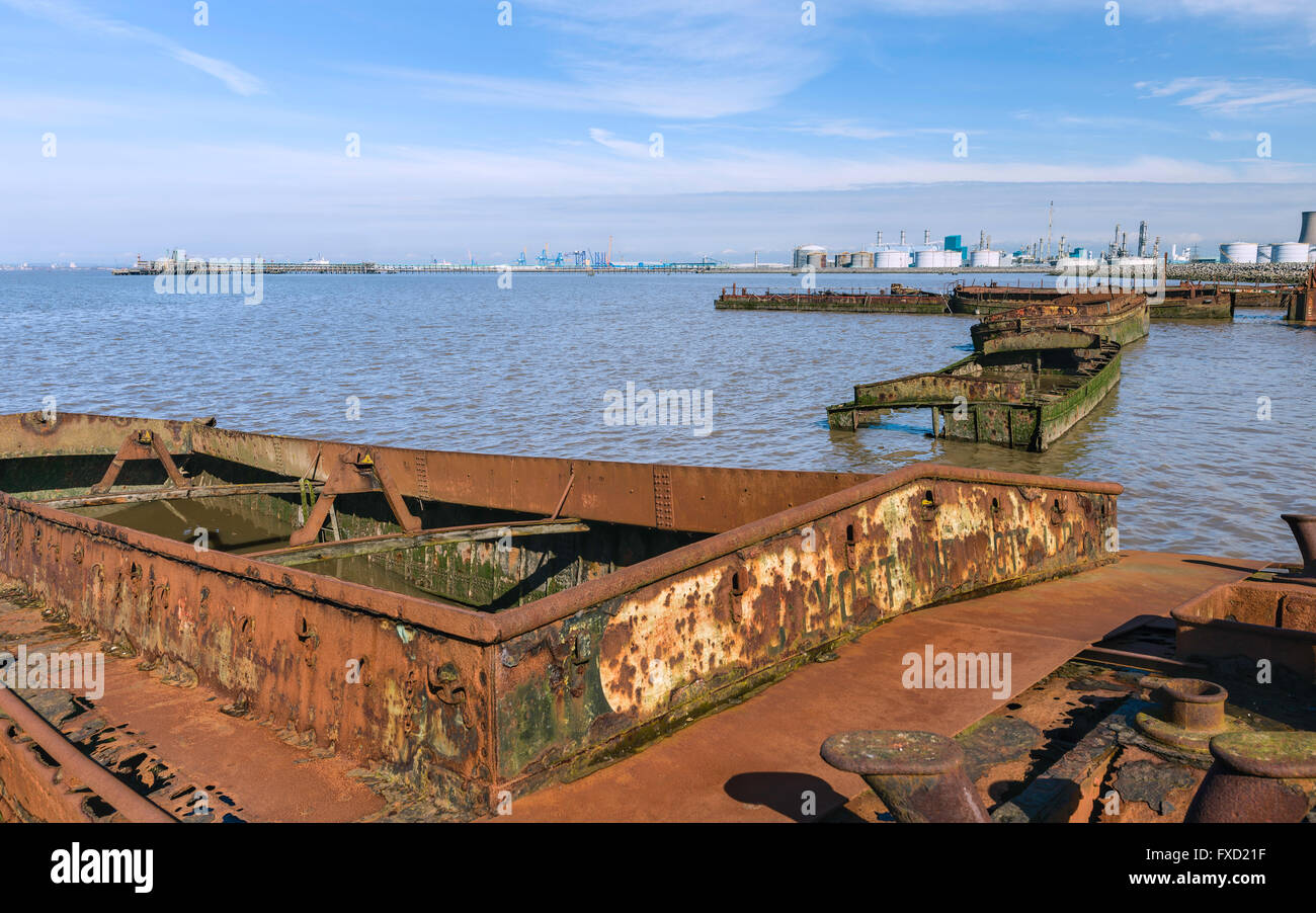 Rusting, obsolete, and abandoned river boats beached on the mud banks of the Humber estuary at high tide. - Stock Image
