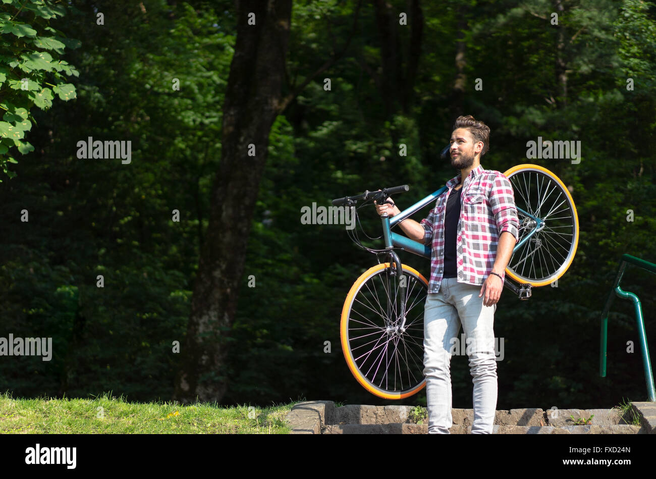 a powerful man hanging his bike on his shoulder, staying on stairs, glancing far away. - Stock Image