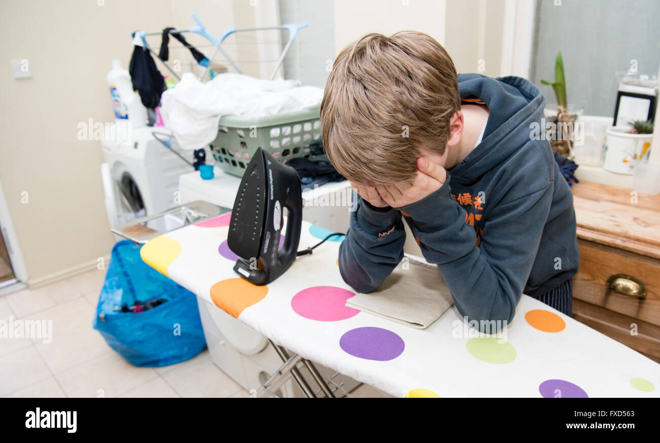 White teenage boy with his head in his hands leaning on a spotty ironing board in a utility room with laundry and - Stock Image