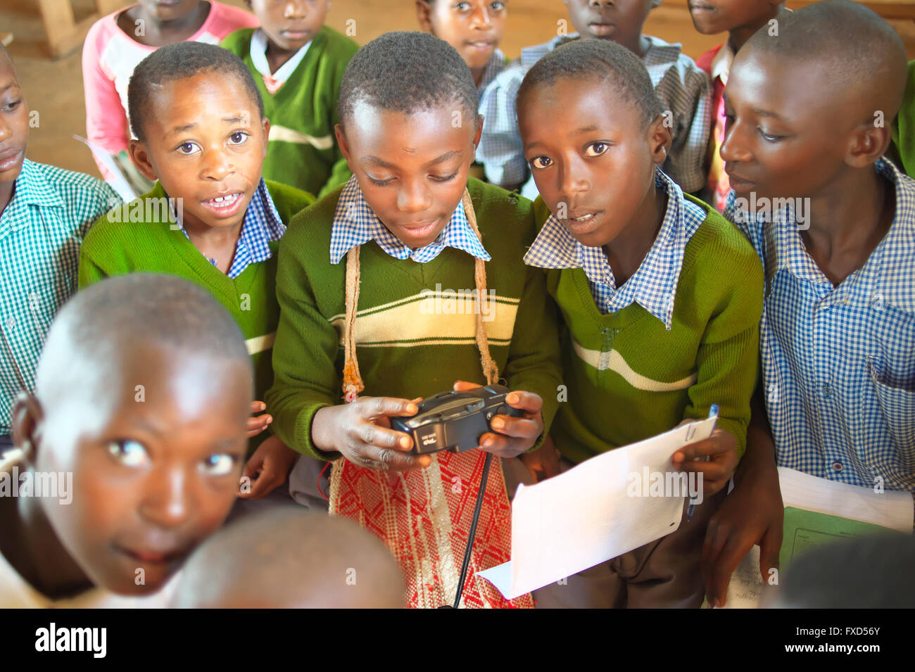 Ugandan school children in uniform at school gather around and study a camera during photography and art lessons - Stock Image