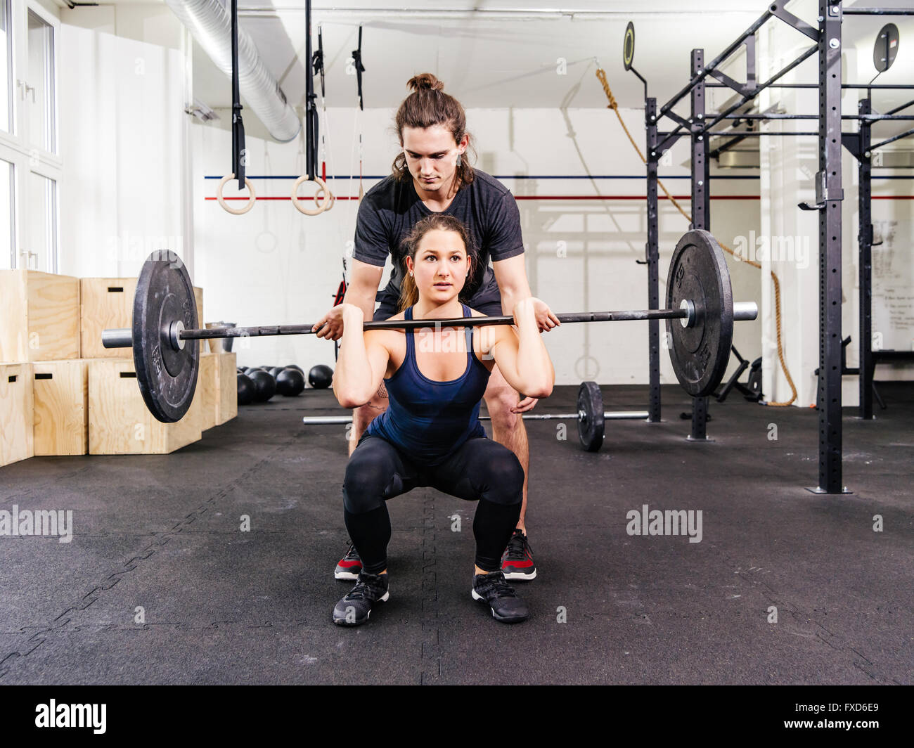 Photo of a young woman at a crossfit gym doing squats while her instructor watches from behind. - Stock Image