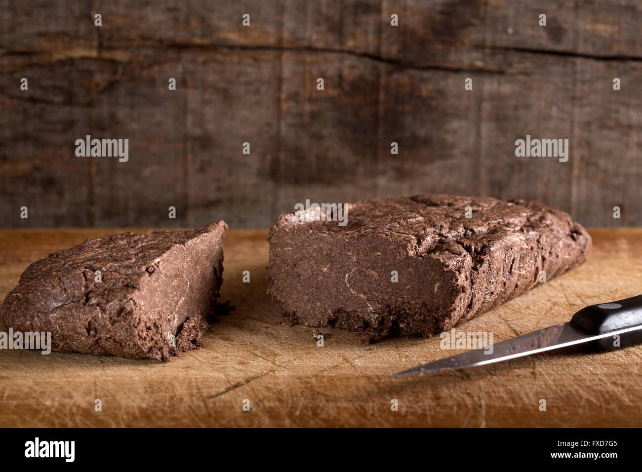 Piece of chocolate halvah over wooden background - Stock Image
