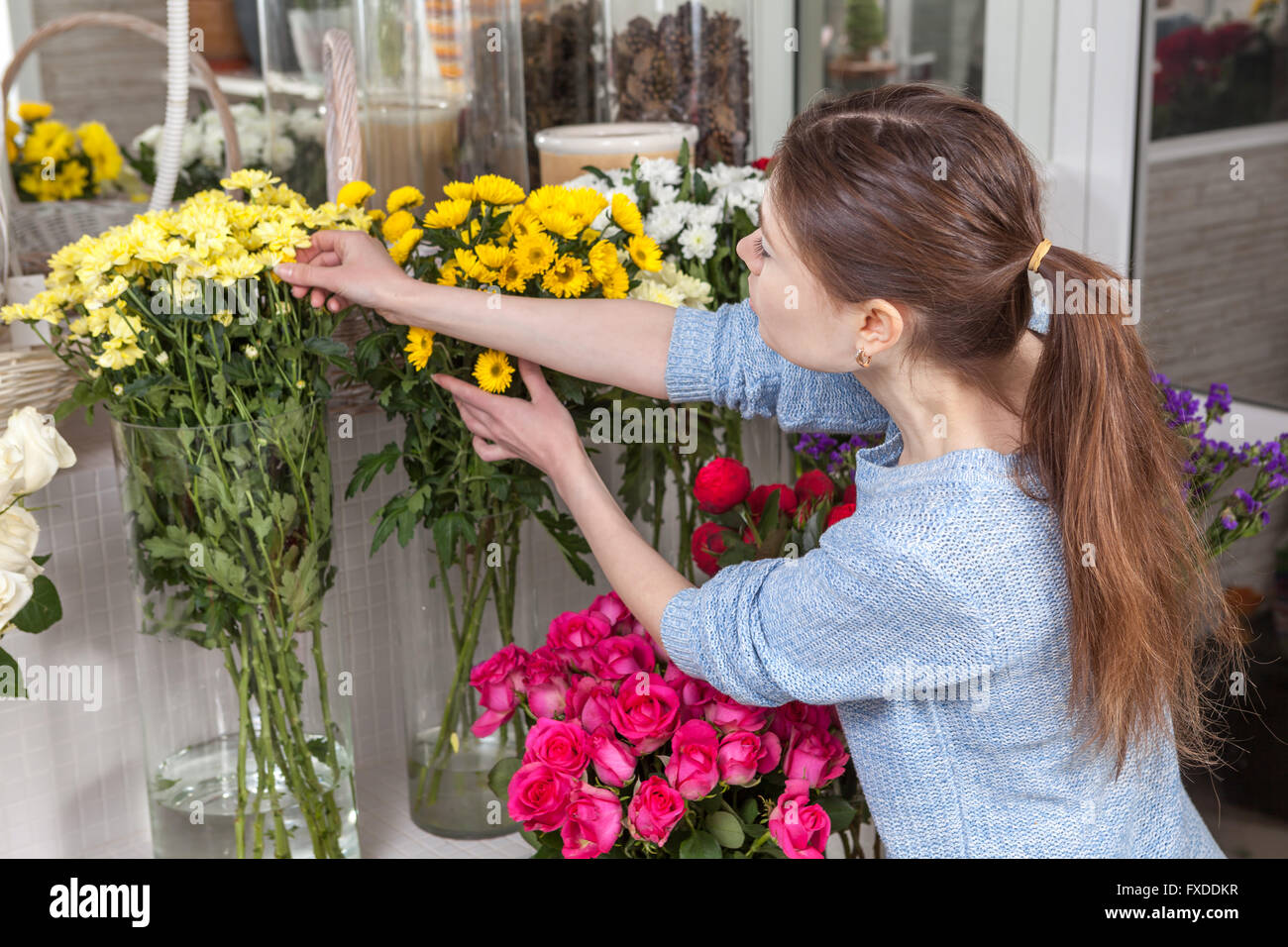 Woman caring for flowers at the shop - Stock Image