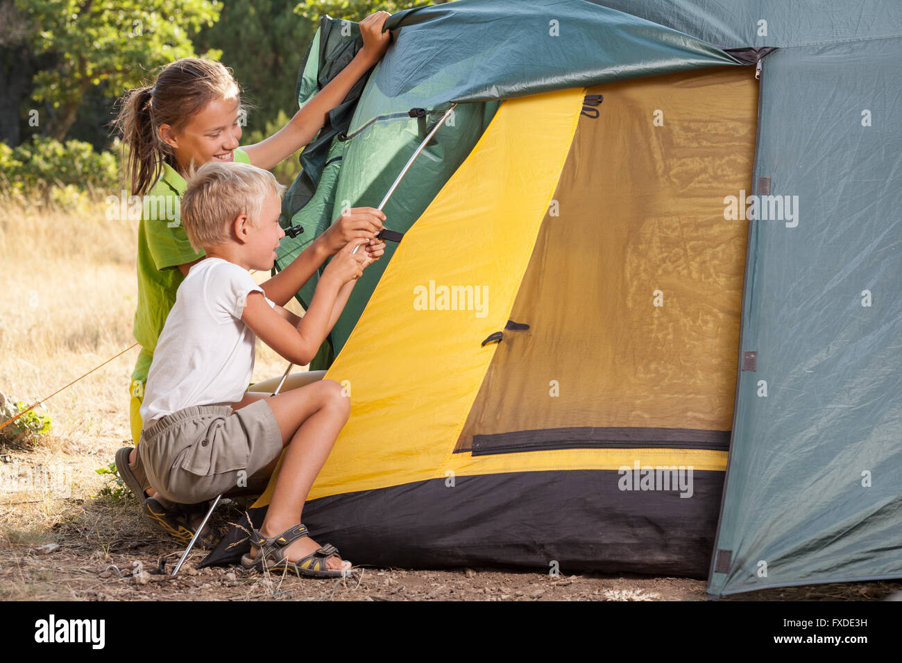 Two children setting a tent - Stock Image