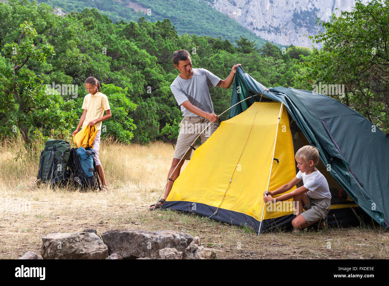 Family setting a tent in the meadow - Stock Image