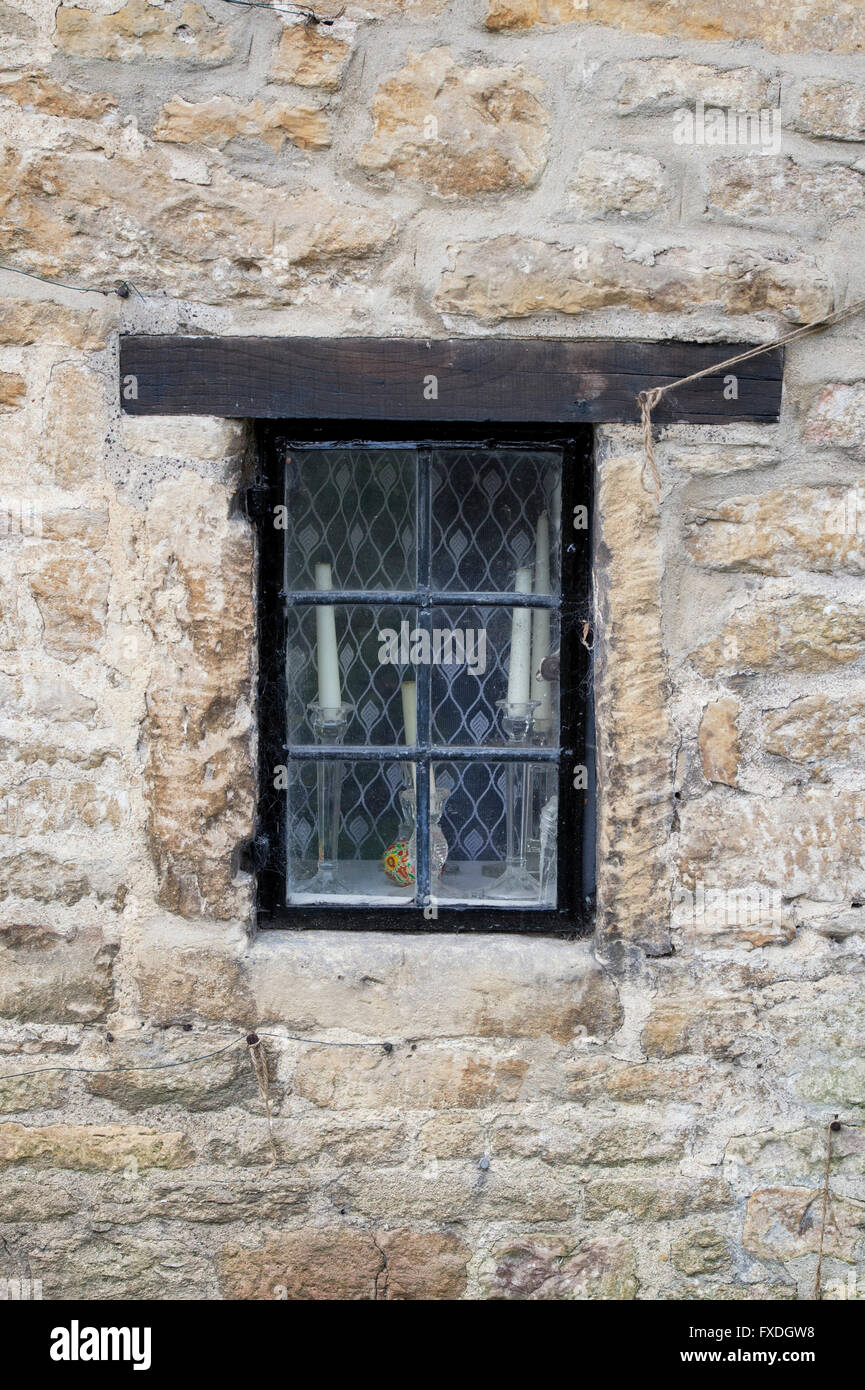 Candles / candlesticks in a cotswold cottage window. Cotswolds, England - Stock Image