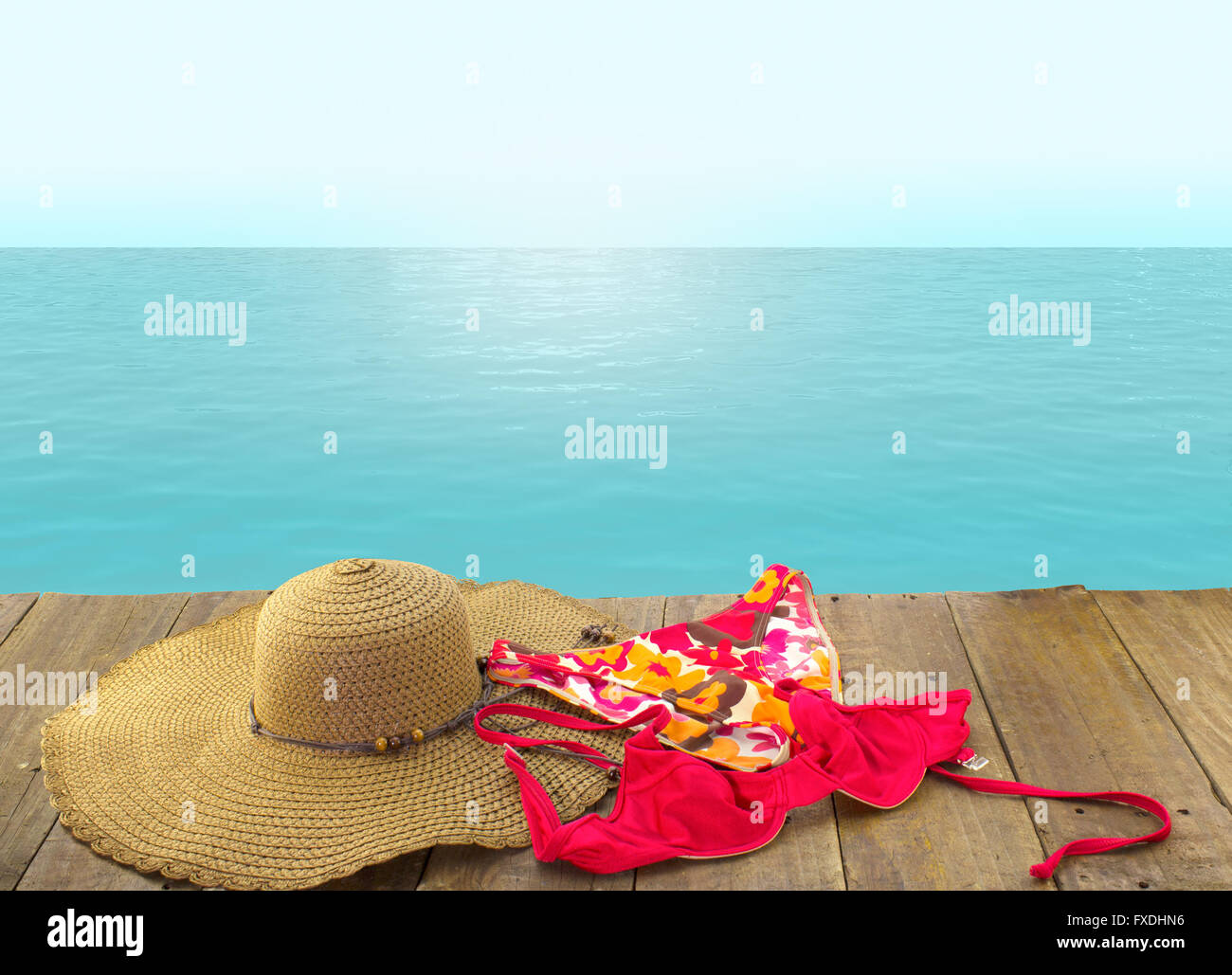 Background with blue ocean, sky and rustic perspective wood pier with bikini and sunhat. - Stock Image