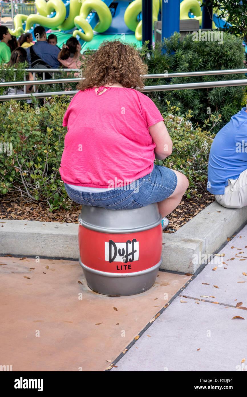 Woman Is Sat On A Duff Bear Barrel At The Simpson TV Area Of Universal Studios Orlando Florida - Stock Image
