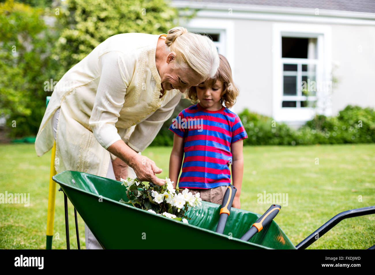 Granny with grandson looking at flowers in wheelbarrow - Stock Image