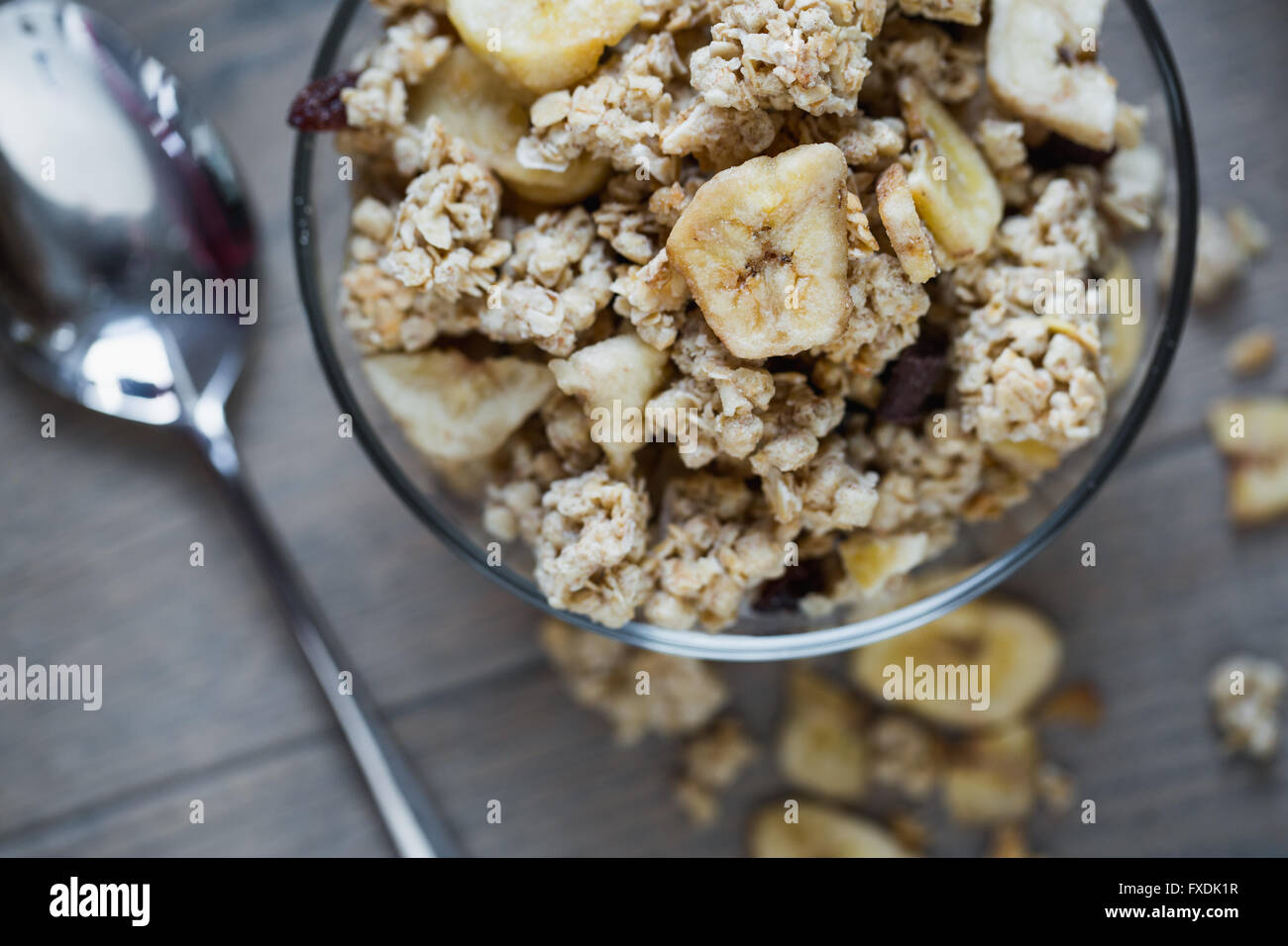 Bowl of granola with banana on wooden table. - Stock Image
