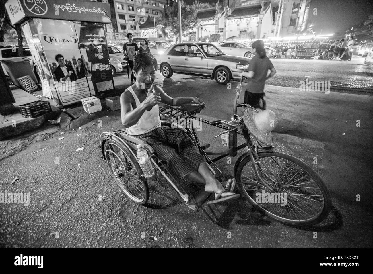 Yangon city, Rangon City, Myanmar, a man with risho in the city, on the street in the evening. - Stock Image