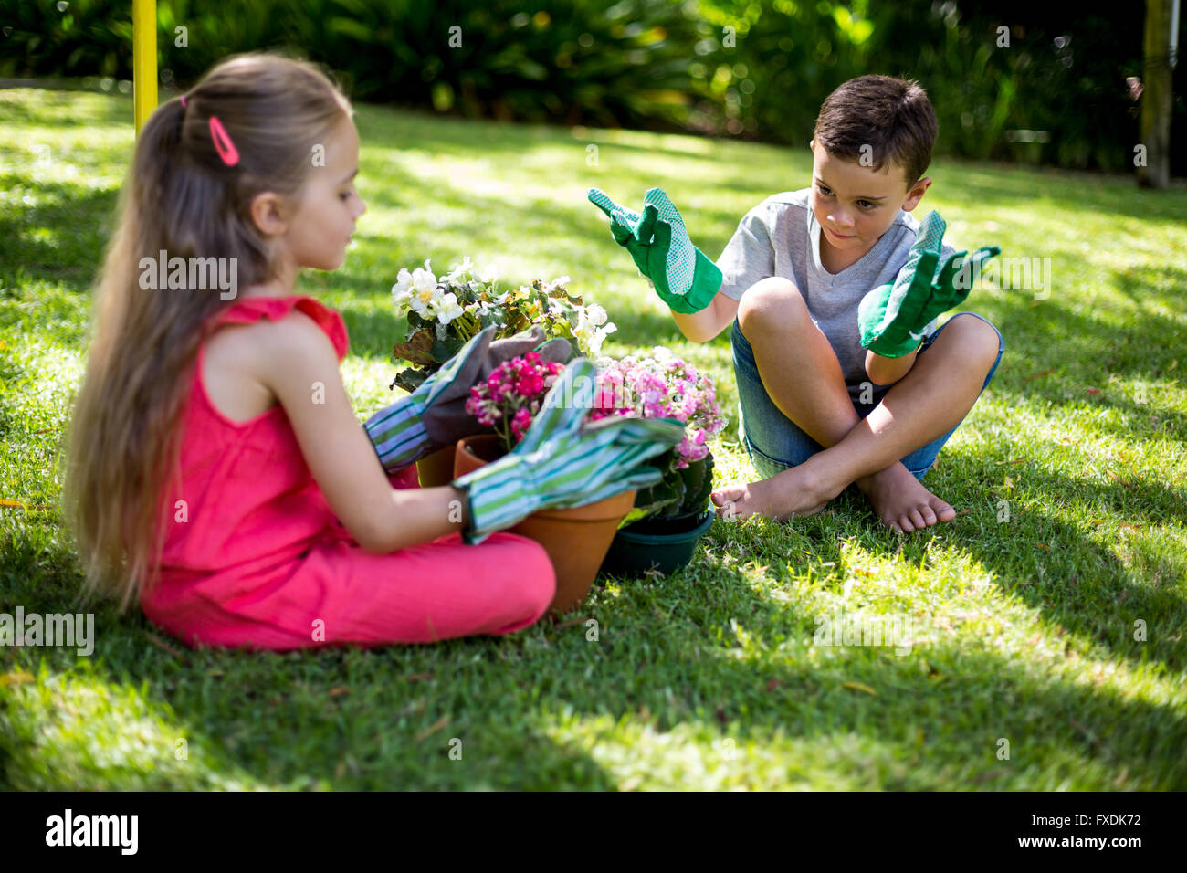 Siblings with flower pots sitting in yard - Stock Image