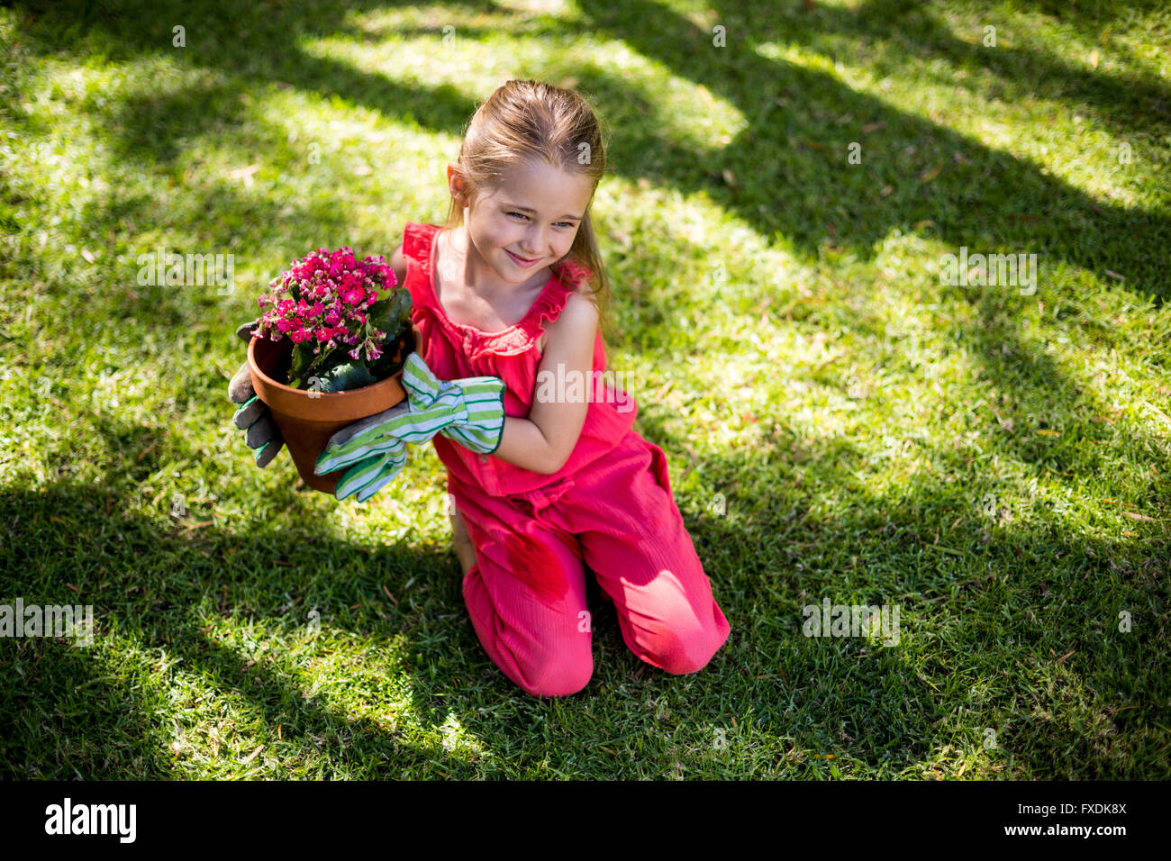 Girl holding flower pot while sitting in yard - Stock Image