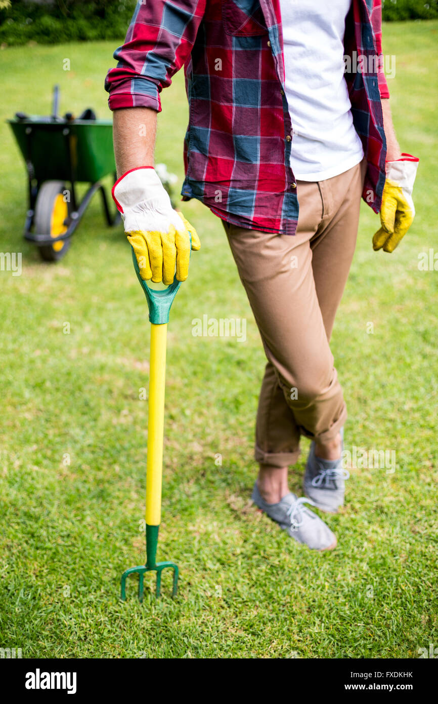 Man standing with rake in yard - Stock Image