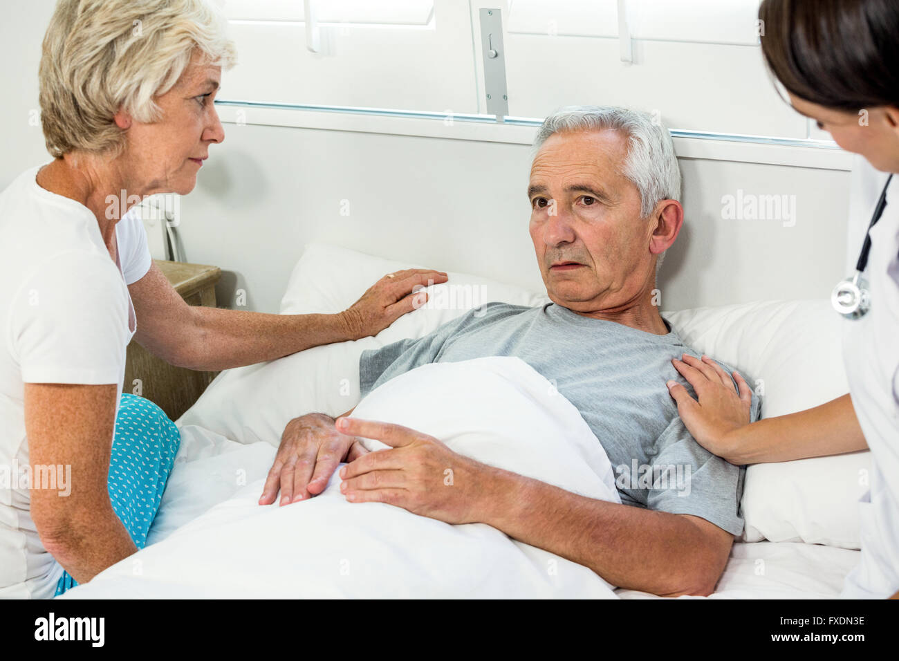 Caregiver and woman comforting senior man - Stock Image