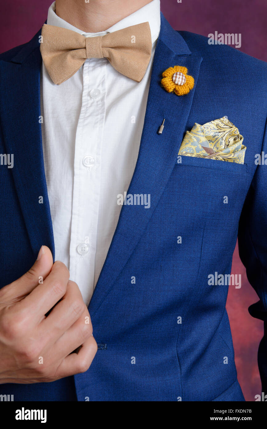 Man in blue suit with brown bow tie, flower brooch, and classic texture pocket square, close up Stock Photo