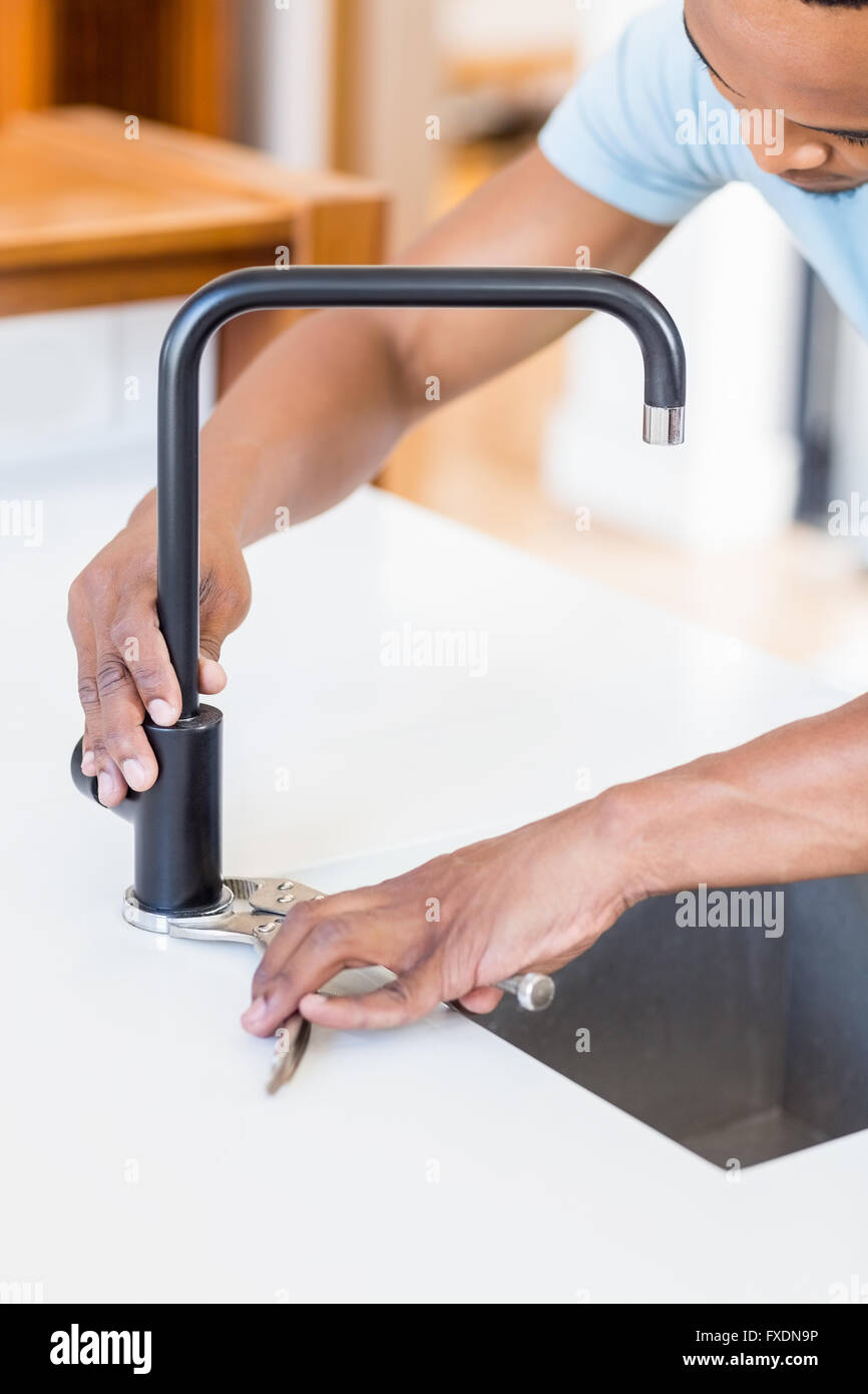 Man tightening tap with a wrench - Stock Image