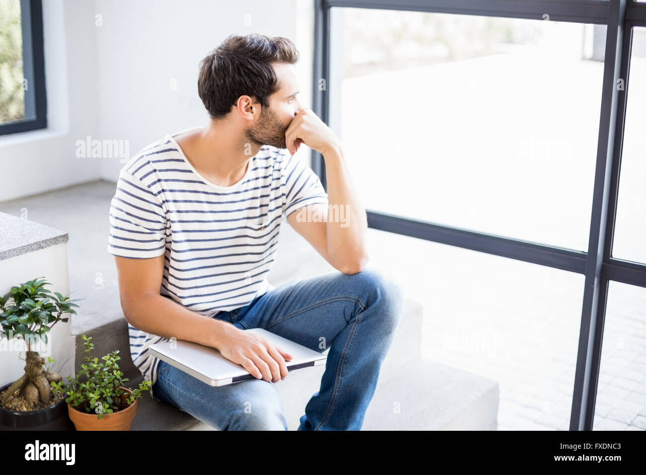 Man sitting with laptop looking out through window - Stock Image