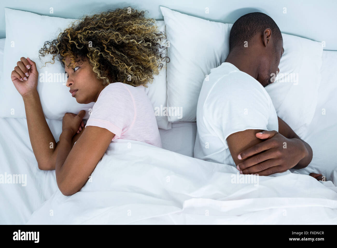 Young couple sleeping back to back and ignoring each other - Stock Image