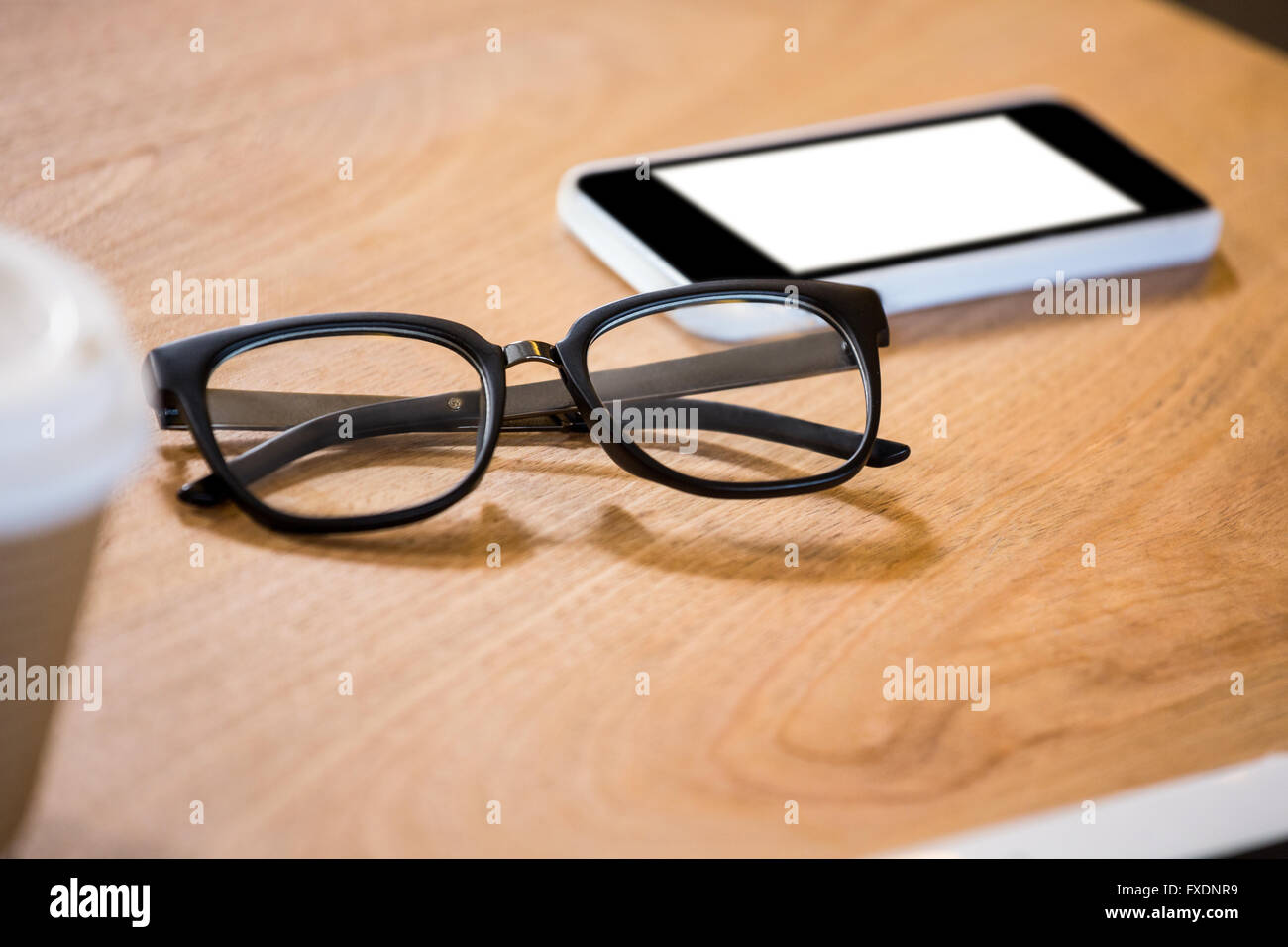 Spectacle and mobile phone on desk - Stock Image