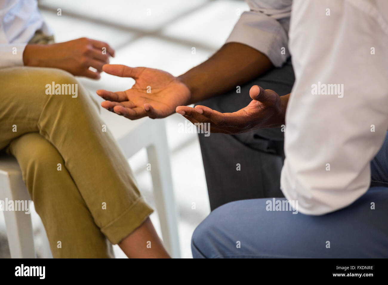 Mid section of businesspeople making hand gesture - Stock Image