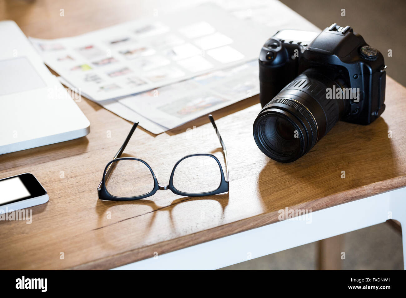 Mobile phone, spectacle and camera on desk - Stock Image