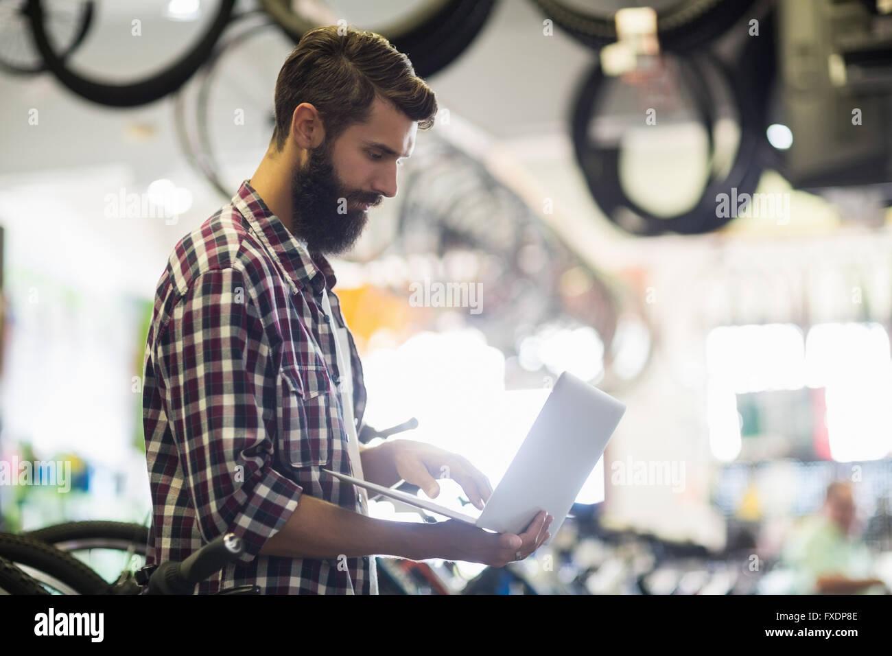 Bike mechanic checking laptop Stock Photo