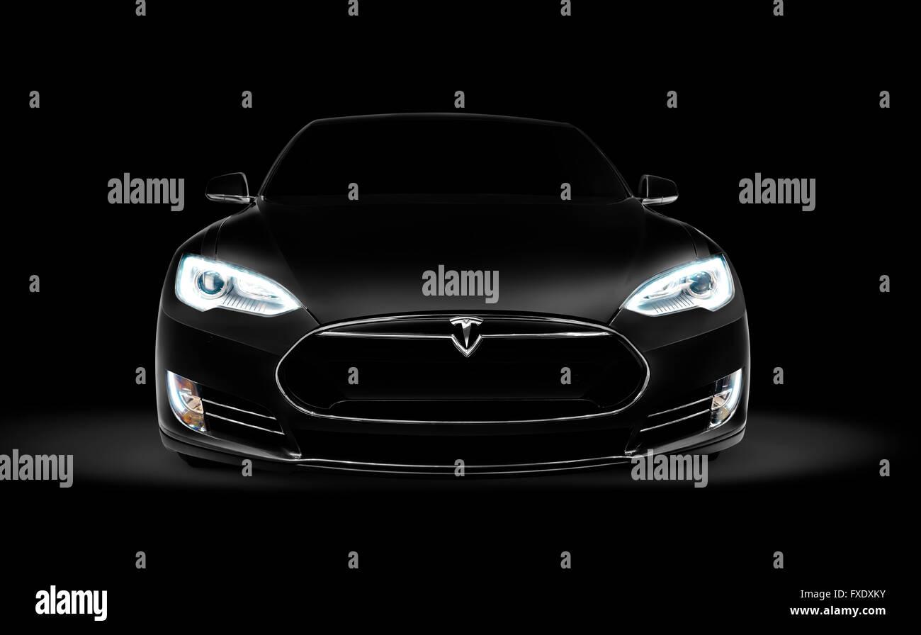 Black 2017 Tesla Model S luxury electric car front view on dark black background - Stock Image