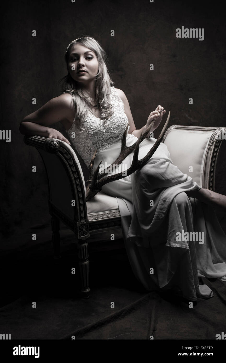 Game of Thrones: A blonde woman girl posing modeling as a classical goddess, holding a pair of antlers - Stock Image