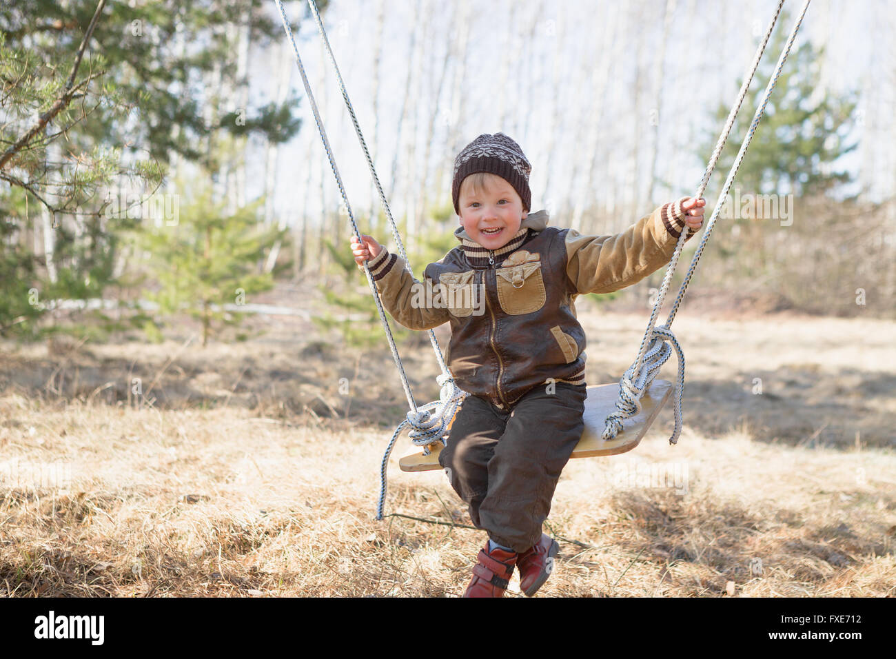 Gomel, Belarus - April 3, 2016: Family in a forest glade ride on a swing. children - Stock Image