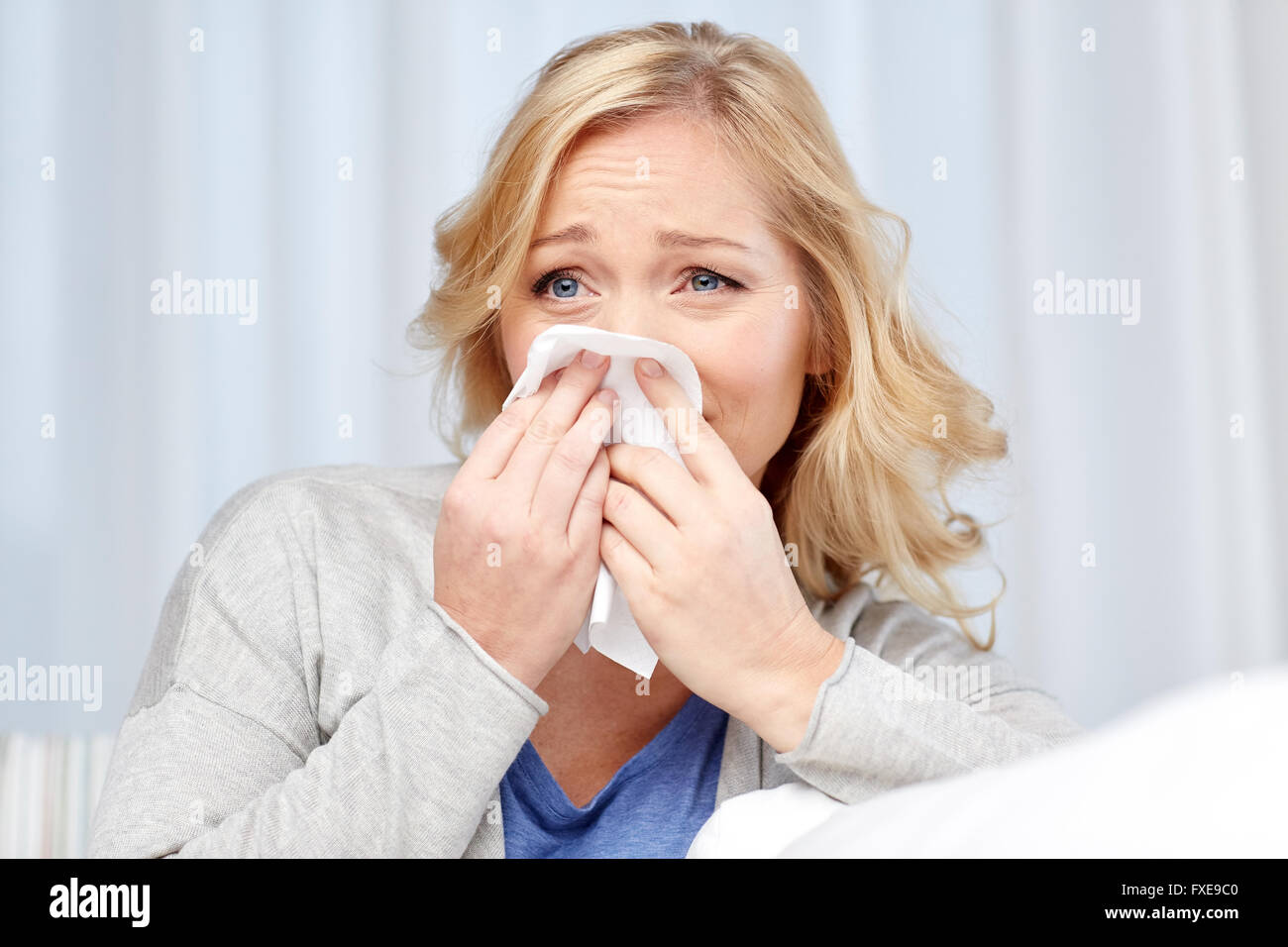 ill woman blowing nose to paper napkin - Stock Image